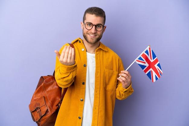 손으로와 서 초대 보라색 벽에 고립 된 영국 국기를 들고 젊은 백인 남자. 와줘서 행복해