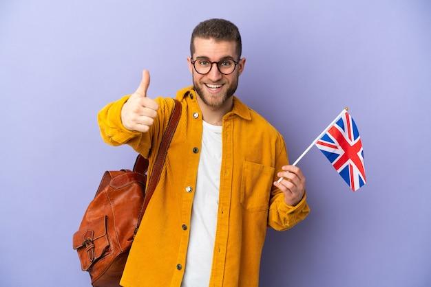 何か良いことが起こったので、親指を立てて紫色で隔離されたイギリスの旗を持っている若い白人男性