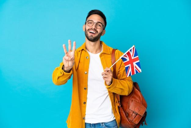 幸せな黄色の背景に分離されたイギリスの旗を保持し、指で3を数える若い白人男性