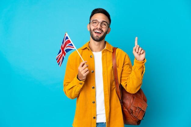 素晴らしいアイデアを指している黄色の背景に分離されたイギリスの旗を保持している若い白人男性