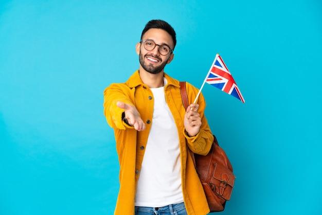 좋은 거래를 닫기 위해 악수하는 노란색 배경에 고립 된 영국 국기를 들고 젊은 백인 남자