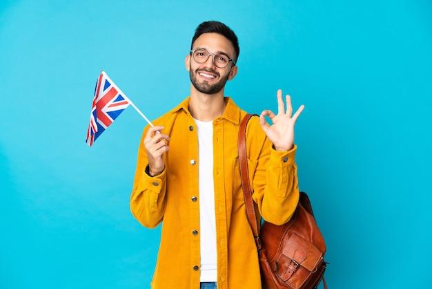 指でokサインを示す黄色の背景に分離されたイギリスの旗を保持している若い白人男性
