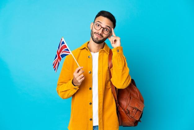 Молодой кавказский мужчина держит флаг соединенного королевства на желтом фоне, думая об идее