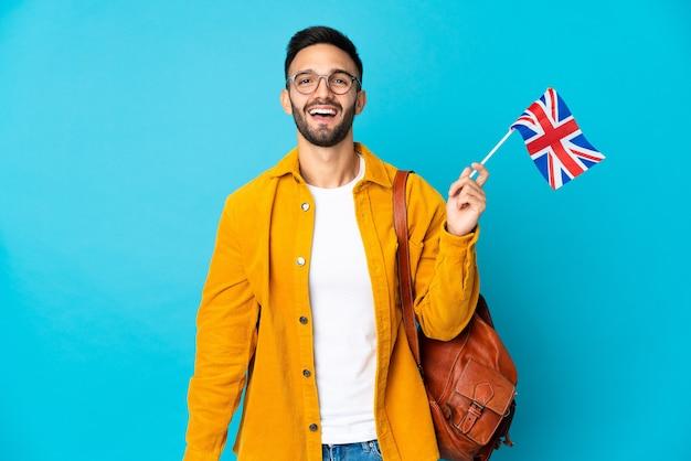 Молодой кавказский мужчина держит флаг соединенного королевства на желтом фоне с удивленным выражением лица