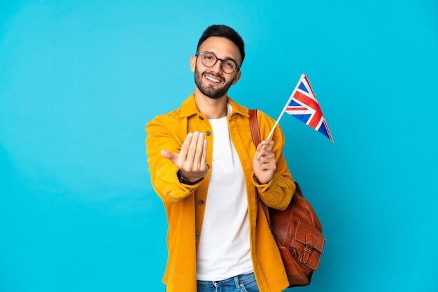 손으로와 서 초대 노란색 벽에 고립 된 영국 국기를 들고 젊은 백인 남자. 와줘서 행복해