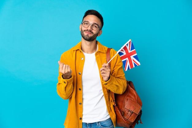 Молодой кавказский мужчина держит флаг соединенного королевства на желтой стене и делает денежный жест