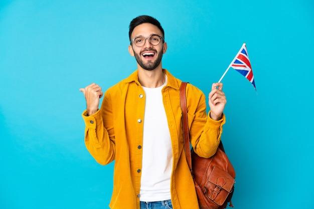 Молодой кавказский мужчина держит флаг соединенного королевства на желтой стене, указывая в сторону, чтобы представить продукт