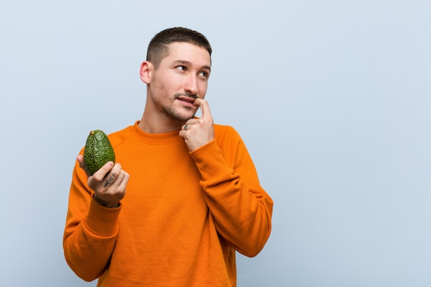 Young caucasian man holding an avocado relaxed thinking about something looking a copyspace.