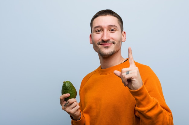 Young caucasian man holding an avocado showing number one with finger.
