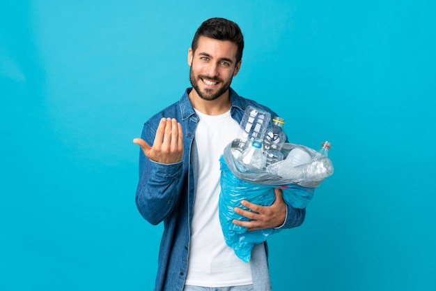 Young caucasian man holding a bag full of plastic bottles to recycle isolated on blue inviting to come with hand. happy that you came