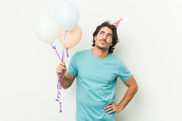 Young caucasian man holding balloons celebrating a birthday isolated in a grey wall