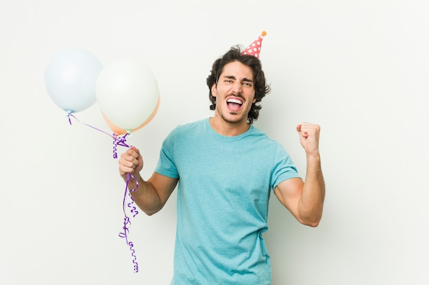 Young caucasian man holding balloons celebrating a brithday isolated in a grey wall