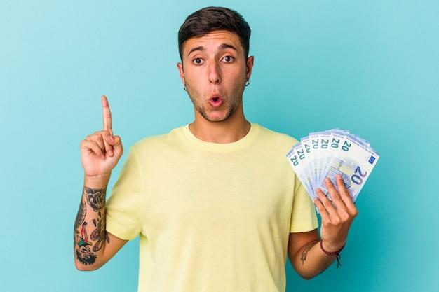 いくつかの素晴らしいアイデア、創造性の概念を持っている青い背景に分離された紙幣を保持している若い白人男性。
