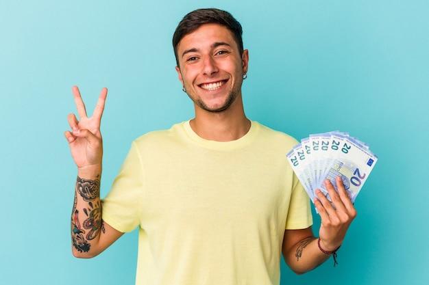 青い背景に分離された紙幣を持っている若い白人男性は、指で平和のシンボルを喜んで気楽に示しています。