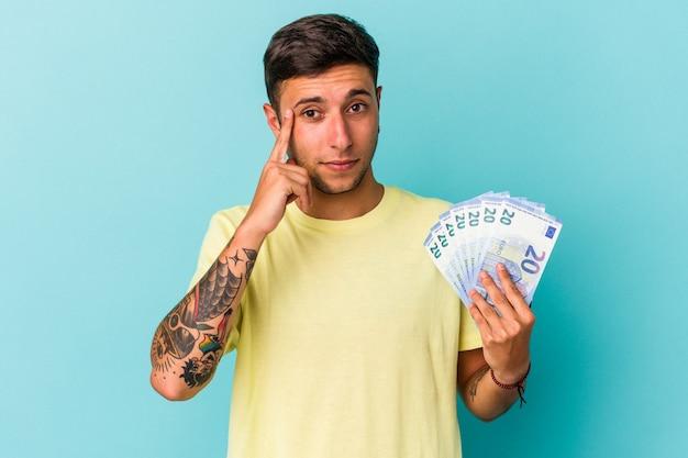 青い背景に分離された紙幣を持っている若い白人男性は、指で寺院を指して、考えて、タスクに焦点を当てた。