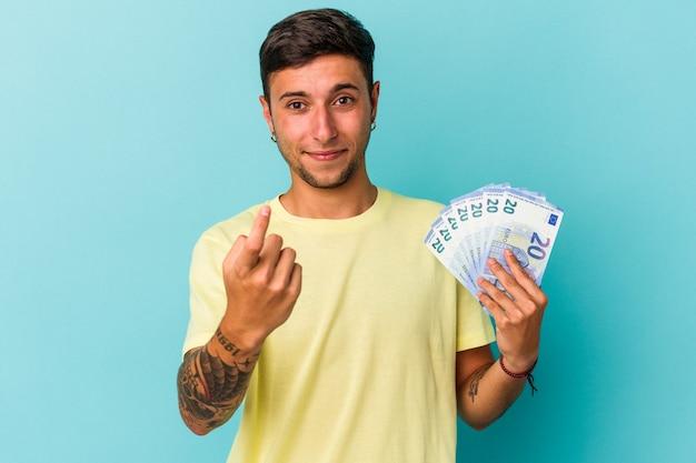 青い背景に分離された紙幣を持っている若い白人男性が、誘うようにあなたに指を向けて近づいています。