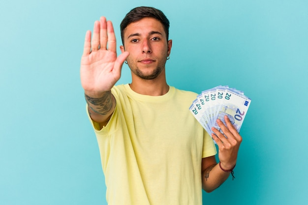 青の背景に分離された紙幣を持っている若い白人男性は、一時停止の標識を示している手を伸ばして立って、あなたを妨げています。