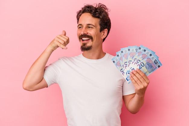 분홍색 배경에 격리된 지폐를 들고 있는 백인 청년은 손가락으로 전화를 걸고 있는 제스처를 보여줍니다.