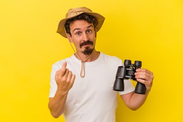 黄色の背景に分離された双眼鏡を持っている若い白人男性が、誘うようにあなたに指を向けて近づいています。