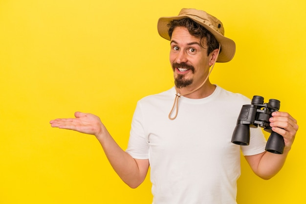 手のひらにコピースペースを示し、腰に別の手を保持している黄色の背景に分離された双眼鏡を保持している若い白人男性。