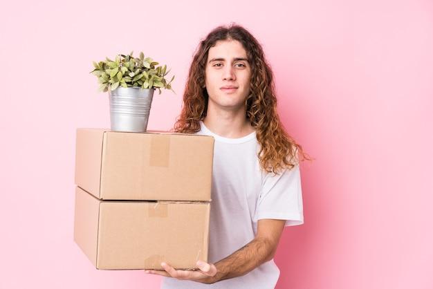 箱を持っている若い白人男性は、幸せ、笑顔、そして陽気に孤立しました。