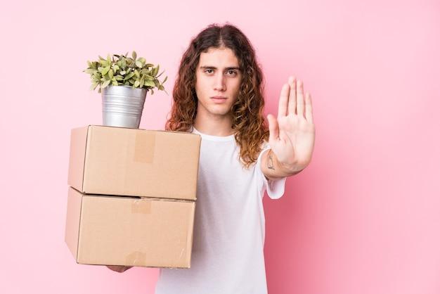 Молодой кавказский человек, держащий коробки, изолировал положение с протянутой рукой, показывая знак остановки, предотвращая вас.