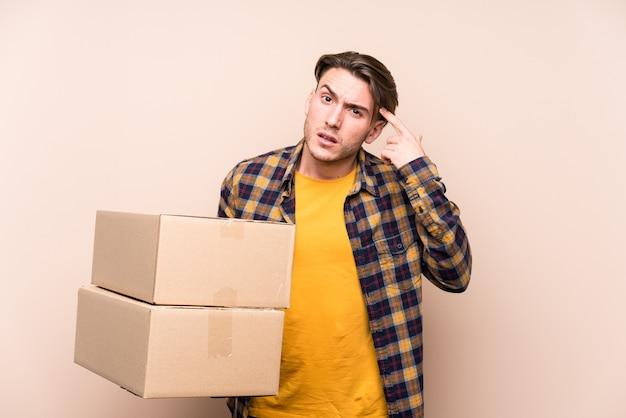 人差し指で失望のジェスチャーを示すボックスを保持している若い白人男性。