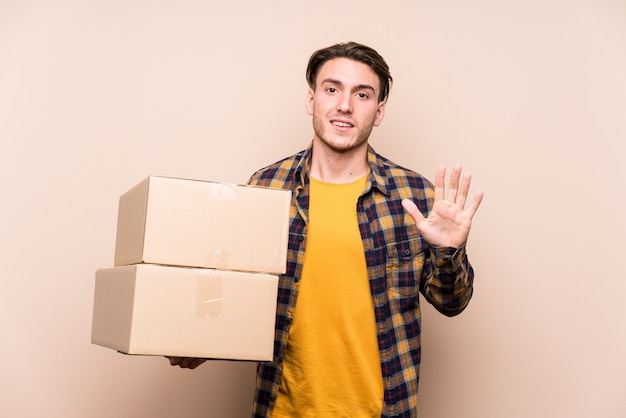 Young caucasian man holding boxes smiling cheerful showing number five with fingers.