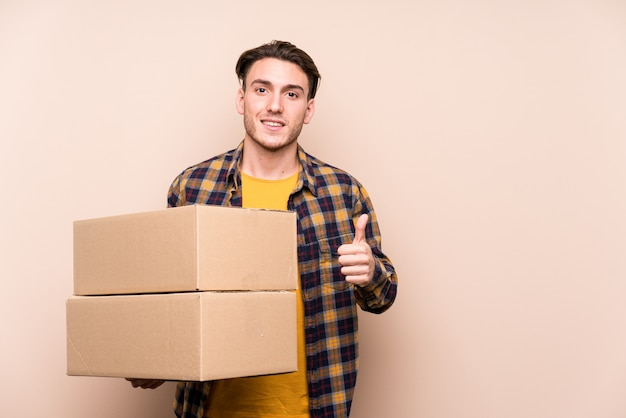 Young caucasian man holding boxes smiling and raising thumb up