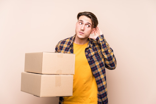 Young caucasian man holding boxes trying to listening a gossip.
