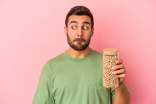 Young caucasian man holding a chickpea bottle isolated on pink background confused, feels doubtful and unsure.