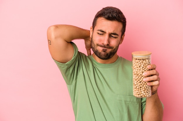 Young caucasian man holding a chickpea bottle isolated on pink background touching back of head, thinking and making a choice.