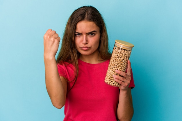 Young caucasian man holding chickpeas jar isolated on white background showing fist to camera, aggressive facial expression.