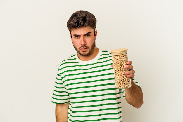 Young caucasian man holding chickpeas jar isolated on white background shrugs shoulders and open eyes confused.