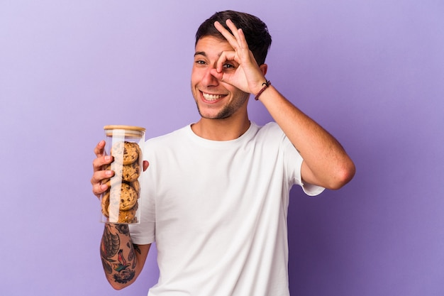 紫色の背景に分離されたチョコレートクッキーを保持している若い白人男性は、目に大丈夫なジェスチャーを維持して興奮しました。