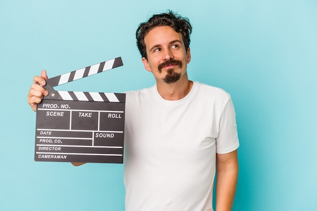 Young caucasian man holding clapperboard isolated on blue background dreaming of achieving goals and purposes