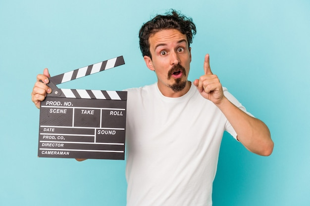 Young caucasian man holding clapperboard isolated on blue background having an idea, inspiration concept.