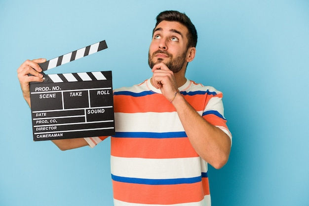 Young caucasian man holding a clapperboard isolated on blue background looking sideways with doubtful and skeptical expression.