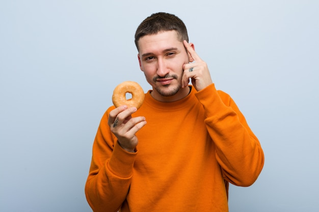Young caucasian man holding a donut pointing his temple with finger, thinking, focused on a task.