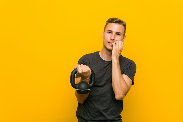 Young caucasian man holding a dumbbell biting fingernails, nervous and very anxious.