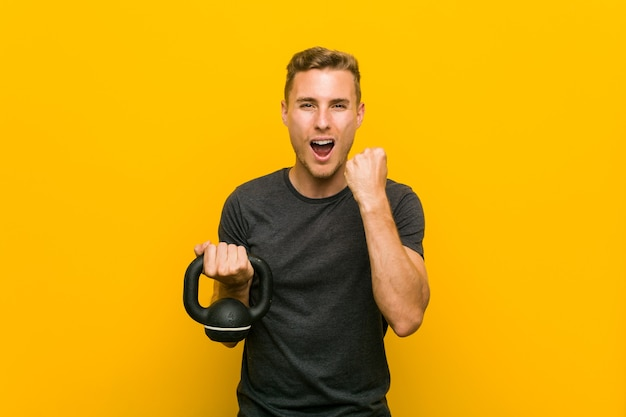 Young caucasian man holding a dumbbell cheering carefree and excited