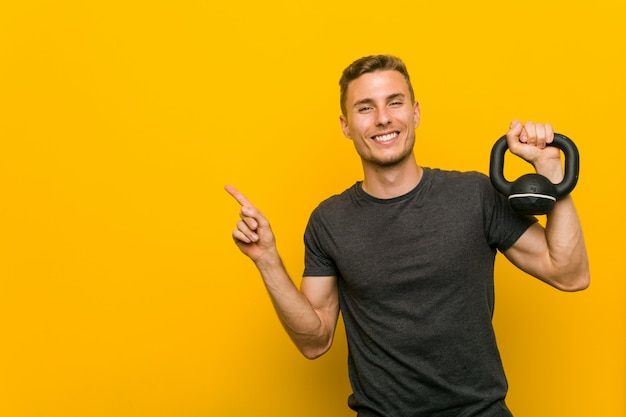 Young caucasian man holding a dumbbell smiling cheerfully pointing with forefinger away.