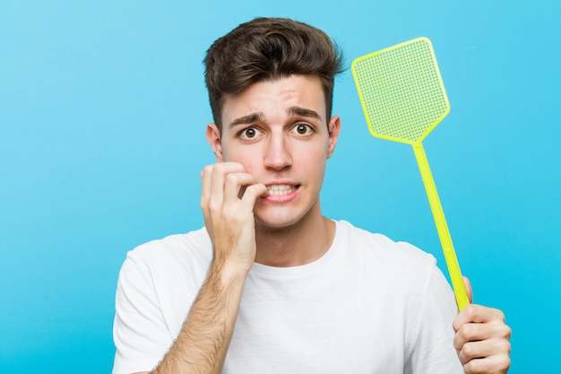 Young caucasian man holding a fly swatter biting fingernails, nervous and very anxious.