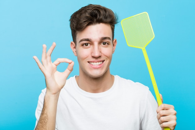 Young caucasian man holding a fly swatter cheerful and confident showing ok gesture.