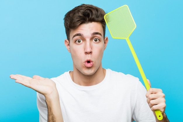 Young caucasian man holding a fly swatter impressed holding copy space on palm.
