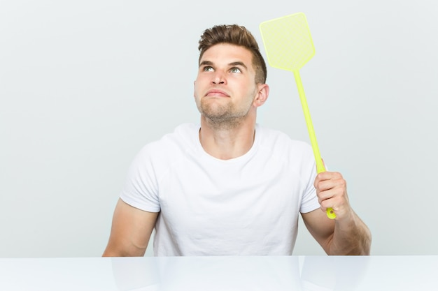 Young caucasian man holding a fly swatter