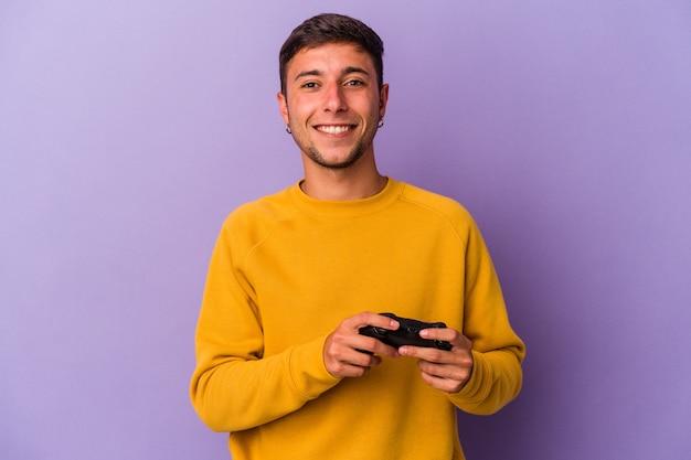 보라색 배경에 격리된 게임 컨트롤러를 들고 있는 백인 청년은 행복하고 웃고 쾌활합니다.