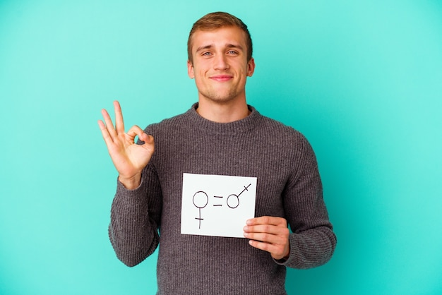Young caucasian man holding a gender equality banner isolated on blue background