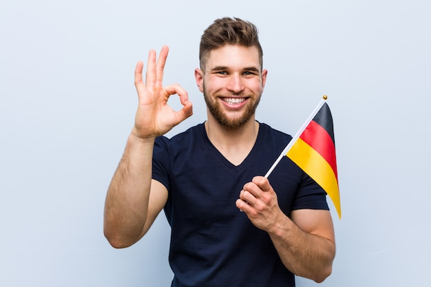 Young caucasian man holding a germany flag cheerful and confident showing ok gesture.