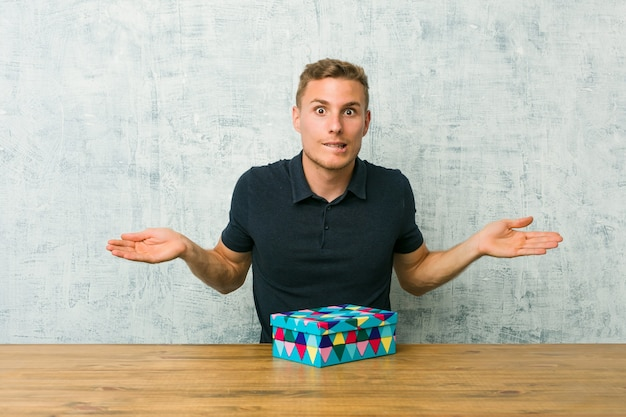 Young caucasian man holding a gift box on a table confused and doubtful shrugging shoulders to hold a copy space.